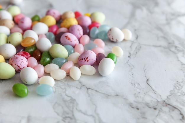 トレンディな灰色の大理石の背景にイースターキャンディチョコレートの卵とジェリービーンズのお菓子