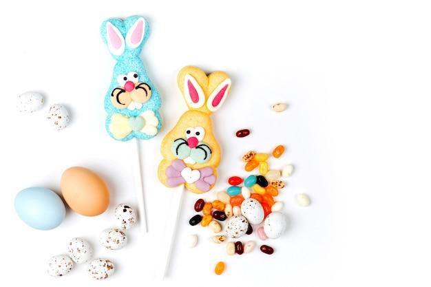 Яичка шоколада конфеты пасхи и jellybean с сладостным зайчиком пасхи на белой предпосылке. плоская планировка, вид сверху