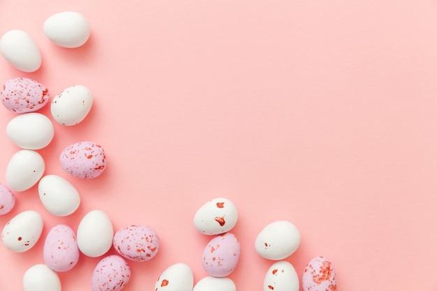 ピンクのテーブルに分離されたイースターキャンディチョコレート卵のお菓子