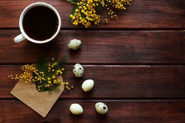 イースターカードミモザの花、ウズラの卵形のお菓子と一杯のコーヒー