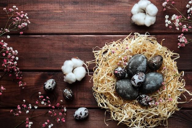 コピースペースのある暗い木製のテーブルに自然に染められた卵と綿の花の装飾が施されたイースターカードの巣