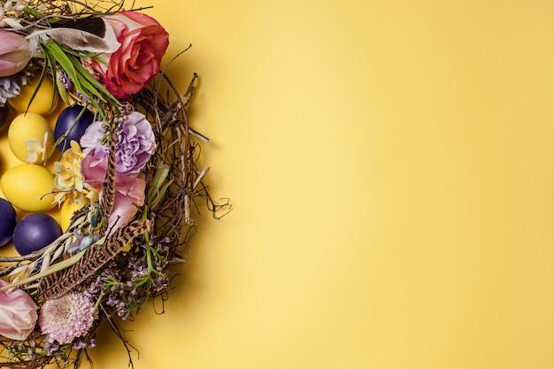 Пасхальная открытка. расписные пасхальные яйца в гнезде на желтом