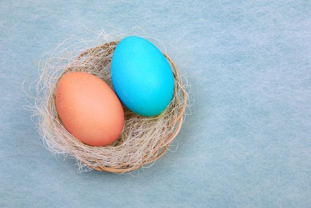 파란색에 작은 고리 버들 세공 바구니에 다채로운 부활절 달걀의 쌍을 가진 부활절 카드