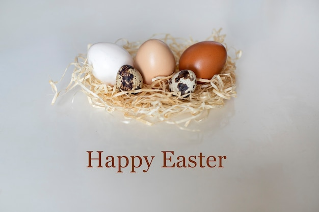 Easter card with the inscription happy easter, and quail and chicken eggs in a wicker nest