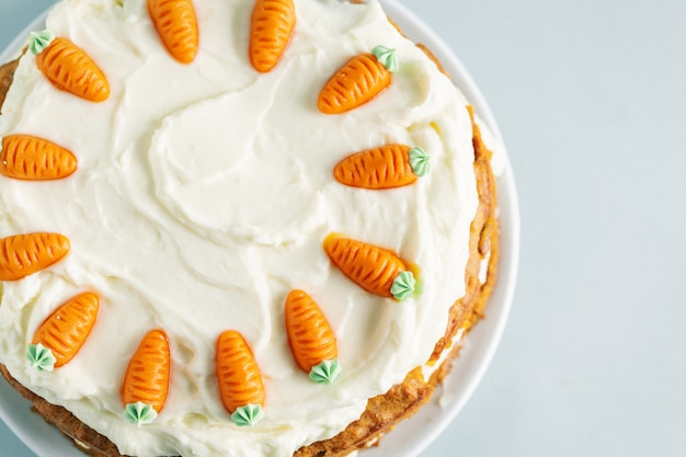 Easter carrot cake with frosting on blue table