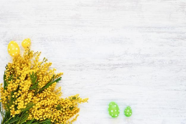 Концепция празднования пасхи. цветы мимозы и пасхальные украшения на белом фоне. копирование пространства, вид сверху.