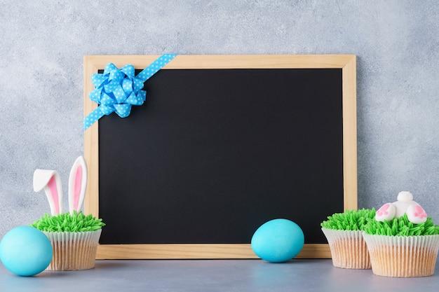 卵とバニーのお尻のカップケーキとイースター黒板の背景。