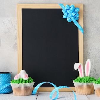 卵と飾られたカップケーキとイースター黒板の背景。