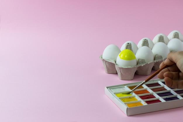 Пасхальные куриные яйца, нарисованные на розовой поверхности