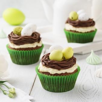 巣とキャンディーの卵で飾られたイースターチョコレートカップケーキ。