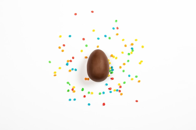 Easter chocolate egg and colorful decorations on a light surface. easter concept, easter treats. flat lay, top view