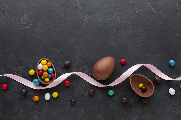 Easter chocolate egg with colorful candy and ribbon