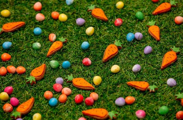 Пасхальные шоколадные яйца и морковное печенье на зеленой траве