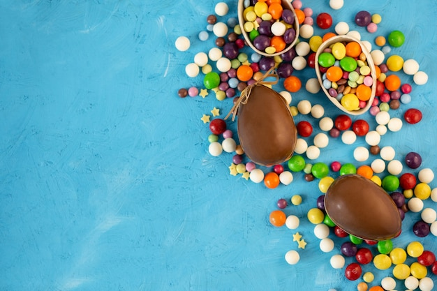 Пасха. шоколадные яйца и цветные конфеты на синем фоне с копией пространства