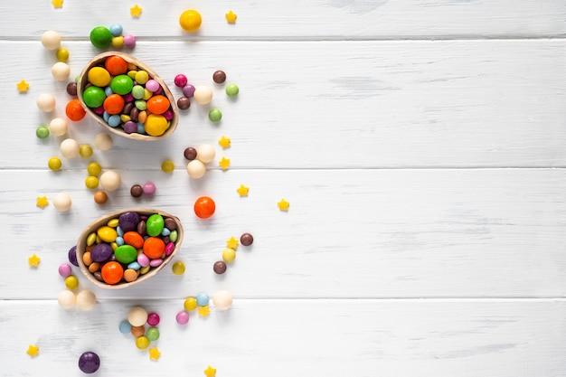 Пасха. шоколадные яйца и цветные конфеты на белом фоне с копией пространства