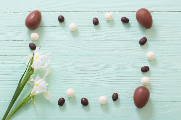 緑の木の表面にイースターチョコレートの卵と花