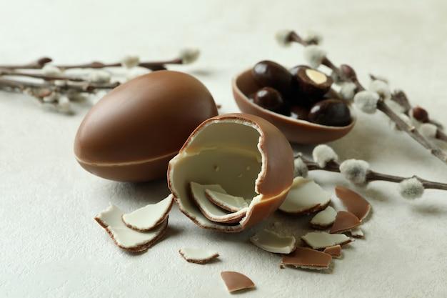 Пасхальные шоколадные яйца и ивовые сережки на белой текстурированной поверхности
