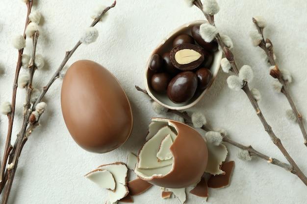 Пасхальные шоколадные яйца и ивовые сережки на белой текстурированной стене