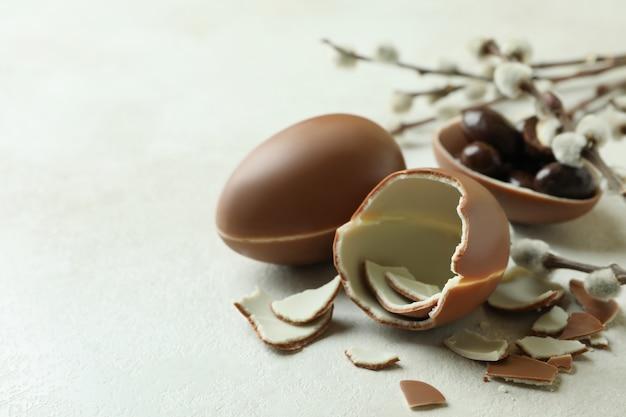 Пасхальные шоколадные яйца и ивовые сережки на белом текстурированном