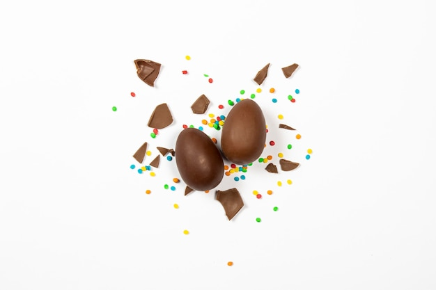 Easter chocolate eggs and colorful decorations on a light surface. easter concept, easter treats. . flat lay, top view