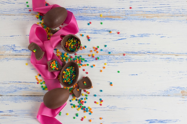 Easter chocolate eggs, pink tape, multicolored sweets on the old white wooden surface. easter concept