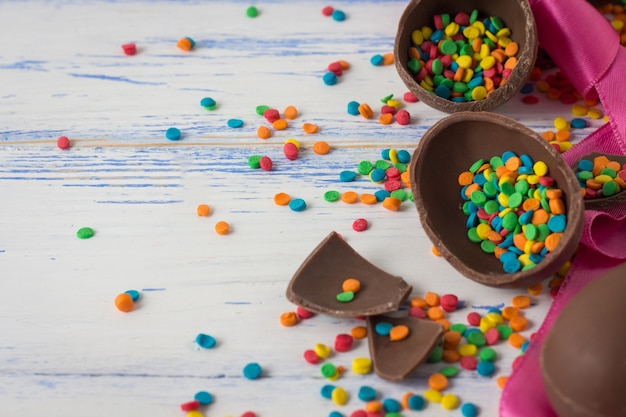 Easter chocolate eggs, pink tape and multicolored sweets on the old white wooden surface. easter concept
