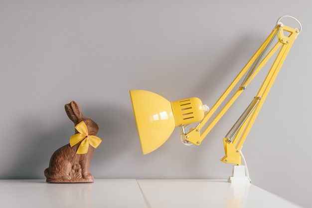 Easter chocolate rabbit with yellow bowtie sitting on table with lamp.
