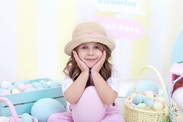 부활절! 부활절 장식 모자에 작은 소녀의 근접 촬영 초상화. 좋은 여자는 부활절 달걀을 사냥. 부활절과 봄 장식, 가족 휴가, 농업. 어린이와 정원. 작은 농부