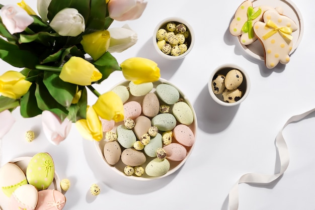 Easter color eggs in a bowl with tulips, flat lay