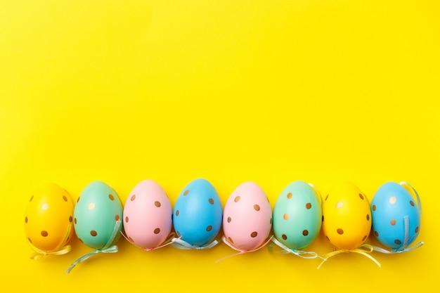 Пасха крашеные яйца границы на желтом фоне. счастливой пасхи поздравительной открытки минимальная концепция. вид сверху, плоская планировка, копия пространства.