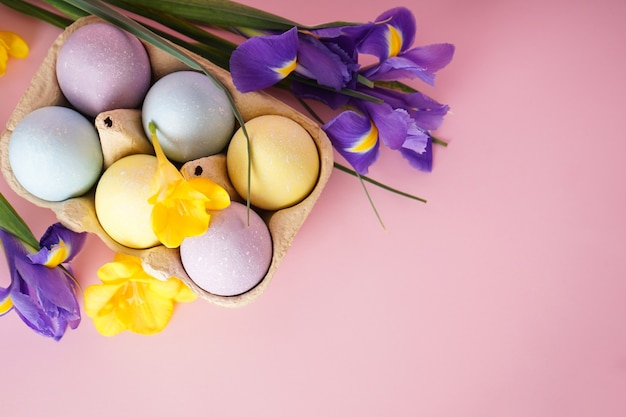 Easter colored eggs in egg tray with flowers on yellow background, place for text. top view.