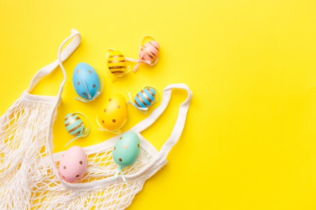 Пасха цветные яйца в сумке на желтом фоне. счастливой пасхи поздравительной открытки концепции. вид сверху, плоская планировка