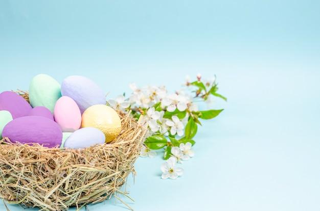 青の干し草で作られた巣のイースター色の卵