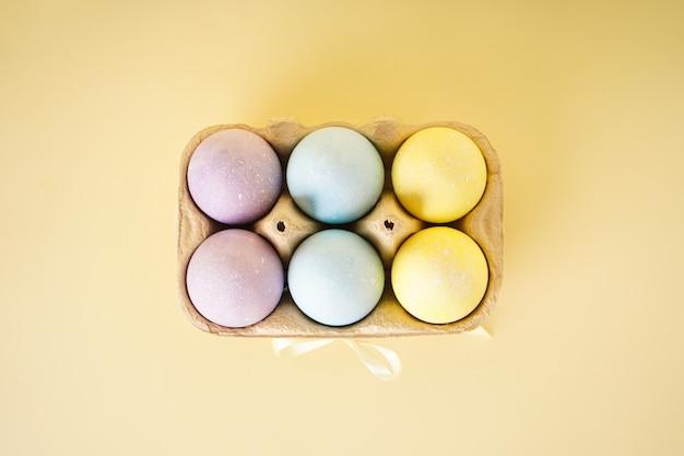 부활절 색 계란 트레이에 노란색 배경. 평면도.