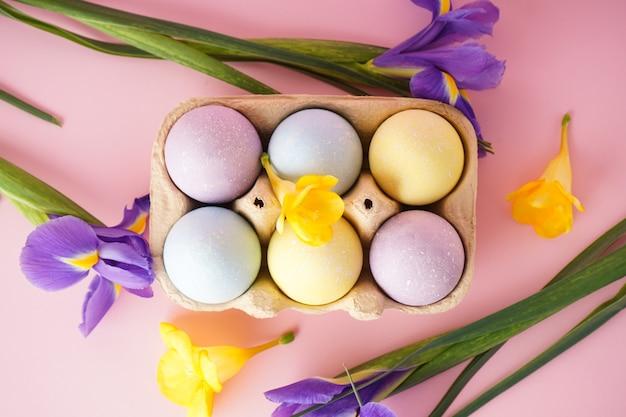 Пасхальные яйца в лотке для яиц с цветами на желтой поверхности. плоская планировка.