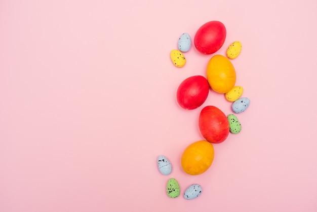 Крашеные пасхальные яйца на розовом фоне. красные и желтые куриные яйца с пастельными перепелиными яйцами.