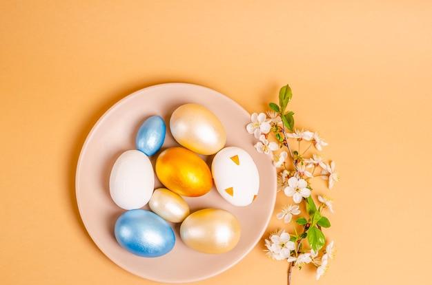 ベージュの背景のプレートにイースター色の卵。季節性のコンセプト、春、はがき、休日。フラットレイ、テキストの場所。上からの眺め。