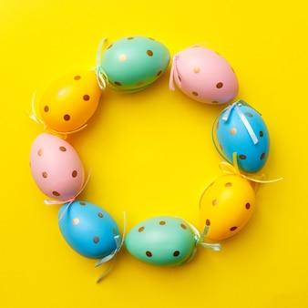 Пасхальные яйца на желтом фоне. счастливой пасхи поздравительной открытки минимальная концепция. вид сверху, плоская планировка, копирование пространства