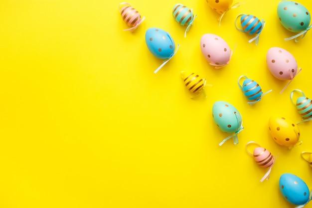 Пасхальные яйца на желтом фоне. счастливой пасхи поздравительной открытки минимальная концепция. вид сверху, плоская планировка