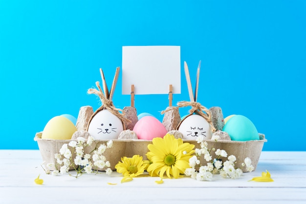 Easter colored eggs in paper tray with decorationd on a blue background