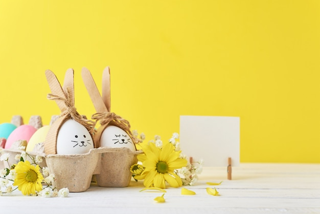 Easter colored eggs in paper tray with decorationd on a yellow background