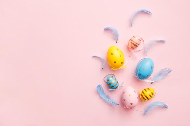 Пасха крашеные яйца с перьями на розовом фоне пастельных. счастливой пасхи поздравительной открытки минимальная концепция. вид сверху, плоская планировка, копирование пространства