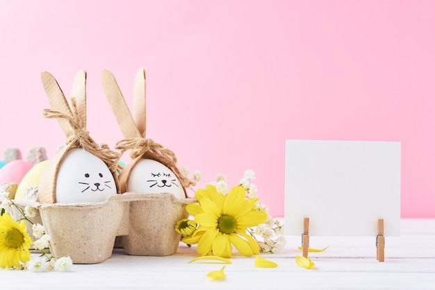 Easter colored eggs with painted faces in paper tray with decorationd on a pink background