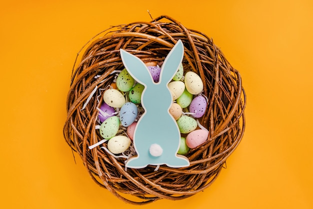 Easter colored eggs and wooden rabbit lie in a wooden wreath on a yellow background