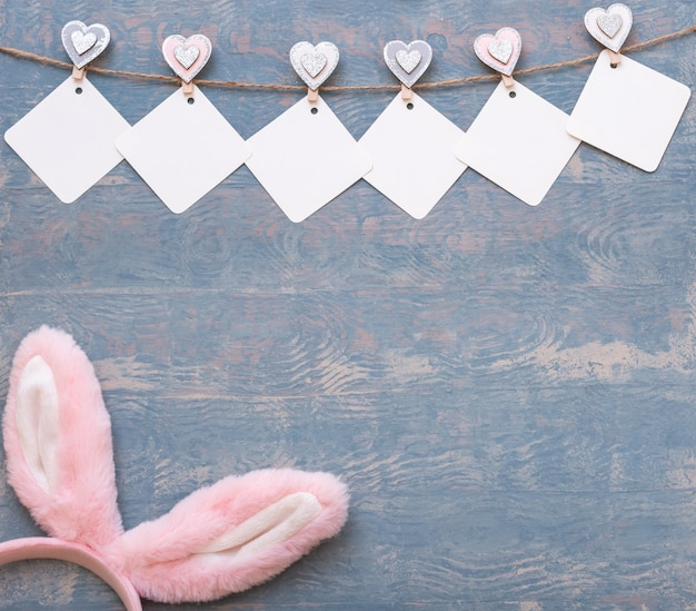 Easter colorful card made of empty garland and easter pink bunny ears on blue wooden background, copy space, flat lay, diy. happy easter concept