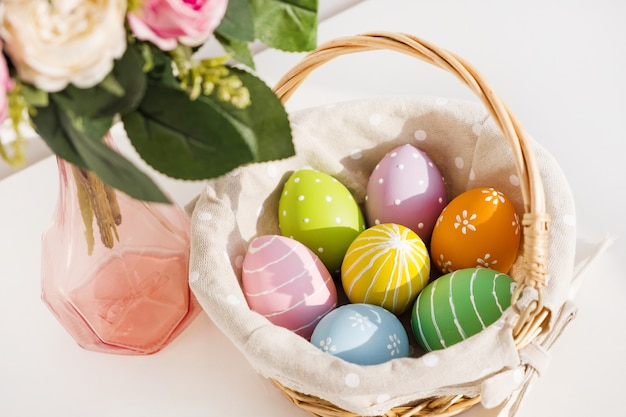 Easter colorful eggs in busket on white wooden table. bouquet of rose flowers on table. happy easter. springtime mood.
