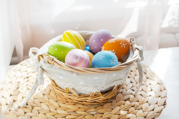 Easter colorful eggs in busket on white wooden table. happy easter table.