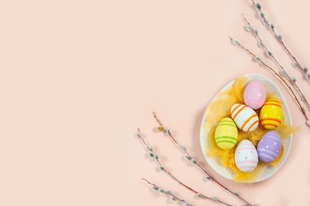 Easter colorful eggs in an eggshaped plate with willow twigs on light background