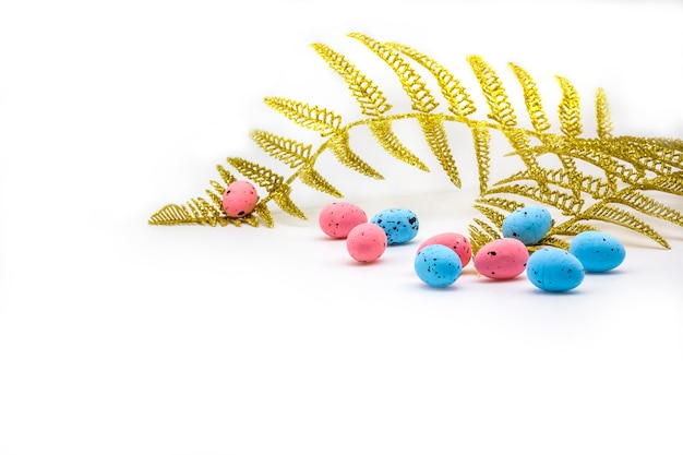 Easter colorful eggs and gold fern branches on white background