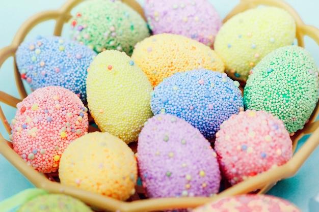 Красочные пасхальные яйца в корзине на синем фоне. пасхальный декор.